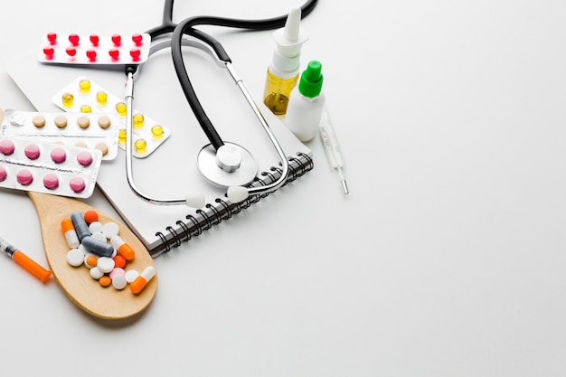 Cuillère en bois remplie de pilules et stéthoscope