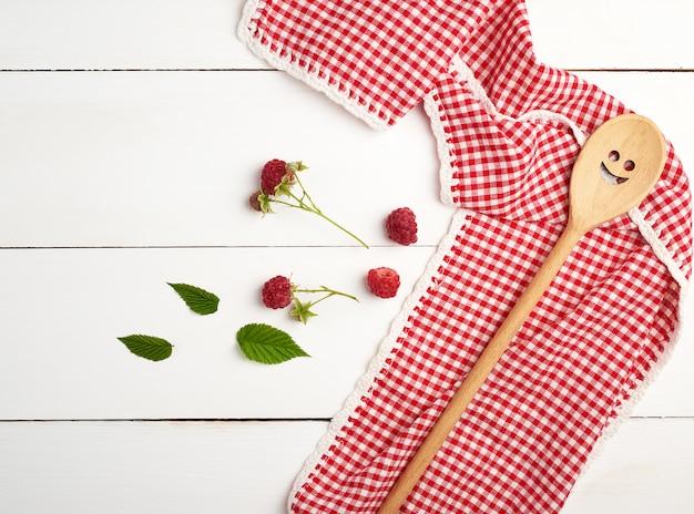 Cuillère en bois et serviette textile rouge sur une table en bois blanche