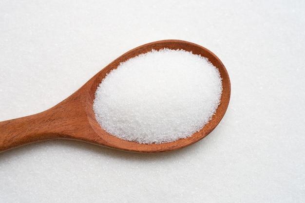 Cuillère en bois avec sucre granulé blanc.