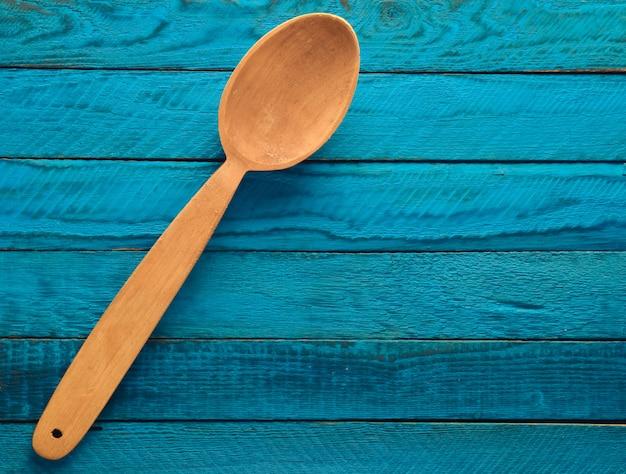 Cuillère en bois sur une table rustique en bois bleue. vue de dessus.