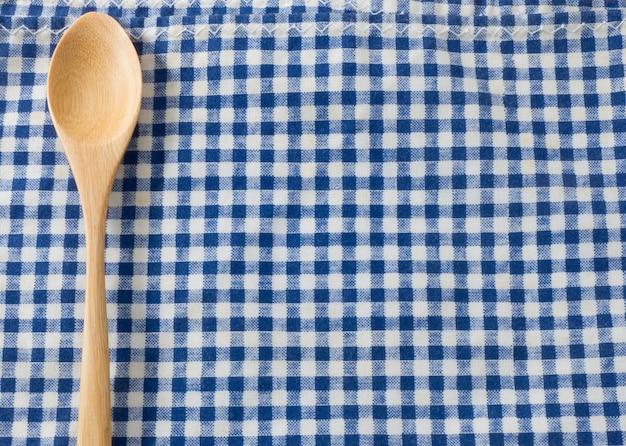 Cuillère en bois d'ustensile en bois de cuisine sur la serviette à carreaux bleue et blanche.