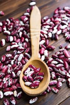 Cuillère en bois et violet à pois sur fond en bois. avalez des haricots. légumes pour une alimentation saine aliments biologiques.