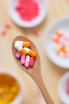 Cuillère en bois vue de dessus avec des pilules
