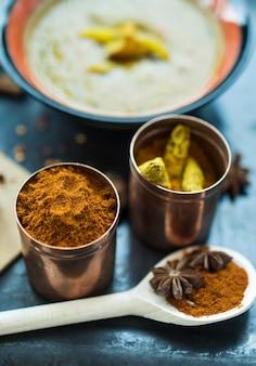 Cuillère et boîtes avec des épices près du plat