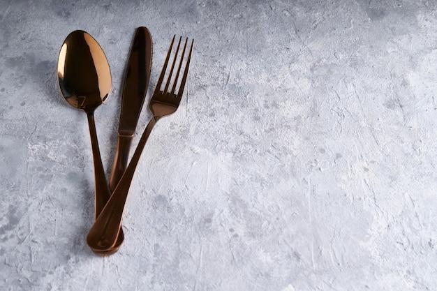 Cuillère en bronze, couteau, fourchette sur une table en pierre claire espace copie
