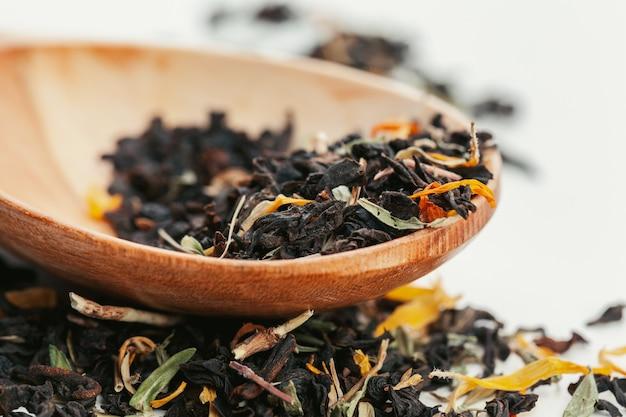Cuillère à café de thé séché sur fond blanc