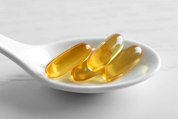 Cuillère avec des capsules d'huile de poisson sur fond de bois blanc