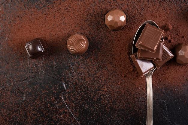 Cuillère avec des carrés de chocolat et des bonbons