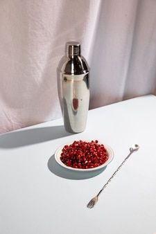 Cuillère à cocktail avec shaker et assiette de graines de grenade au-dessus d'un bureau blanc