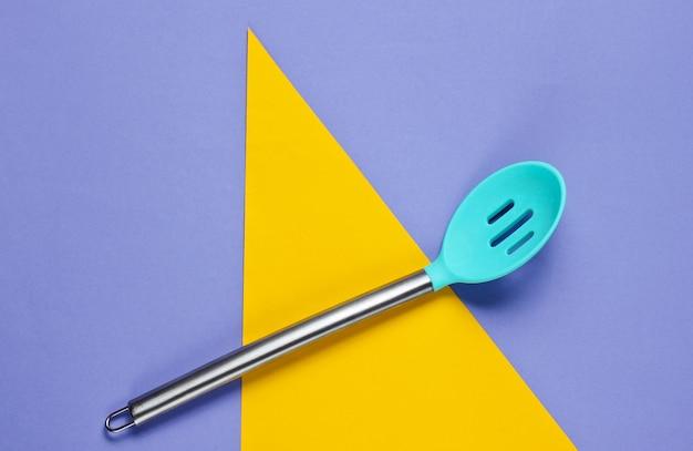 Cuillère de cuisine sur violet avec des formes géométriques