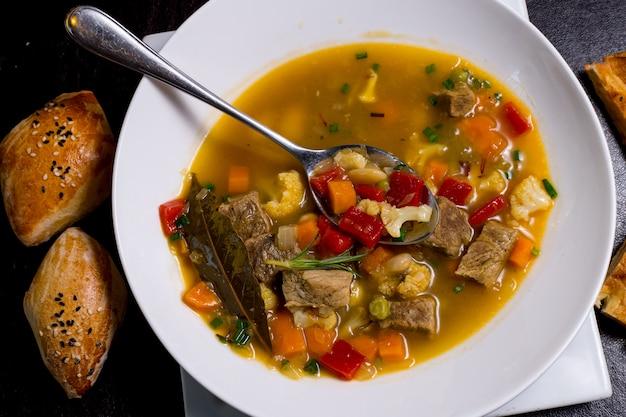 Cuillère dans l'assiette haricots soupe viande carotte pomme de terre vert tomate vue de dessus