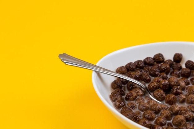 Cuillère dans un bol blanc avec des boules de céréales de maïs au chocolat et du lait sur jaune