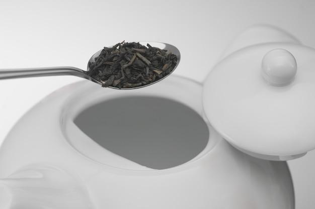Cuillère avec des feuilles de thé et une théière en céramique blanche, prise de vue macro