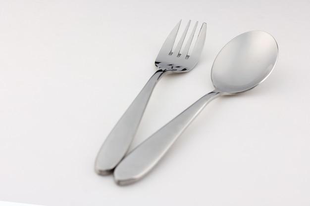 Cuillère et fourchette en argent en acier et acier inoxydable placés sur un fond blanc.