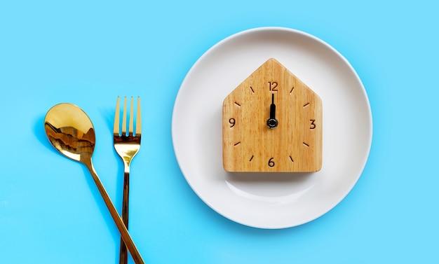 Cuillère et fourchette dorées sur bleu. copier l'espace