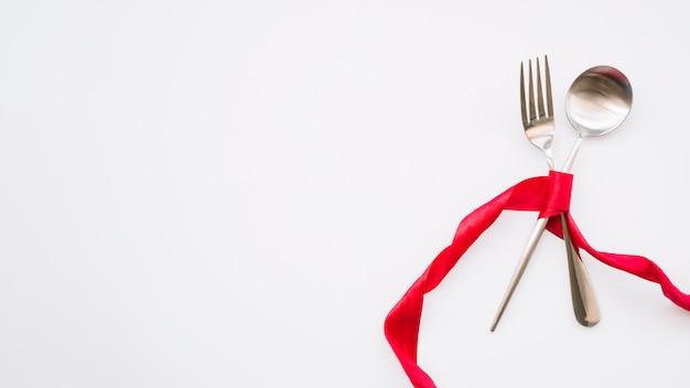 Cuillère et une fourchette avec ruban rouge