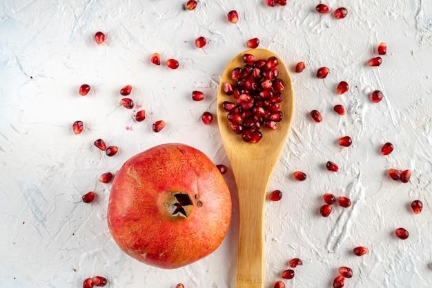 Une cuillère avec des fruits de grenade à plat avec des graines et des grains sur la table à plat
