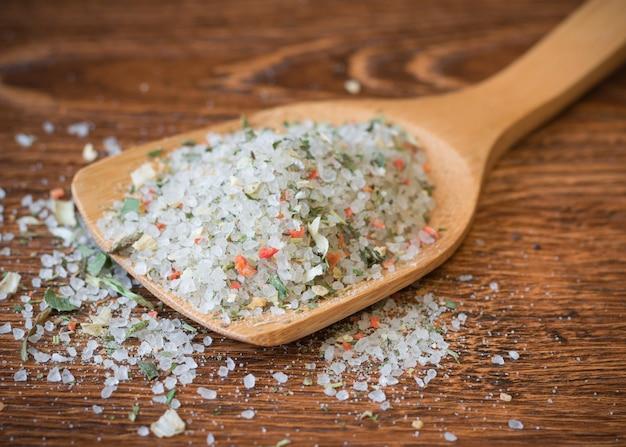Cuillère de gros sel et d'épices sur une table en bois.