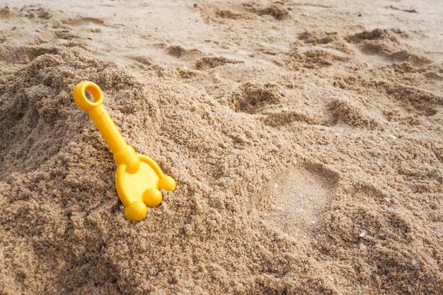 Cuillère jaune pour enfant sur la plage