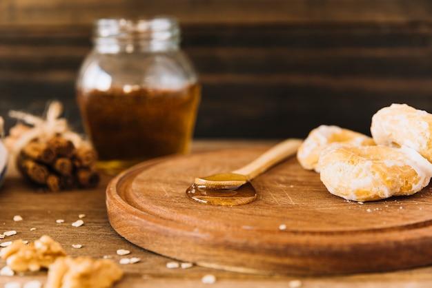 Cuillère de miel et beignet sur planche de bois