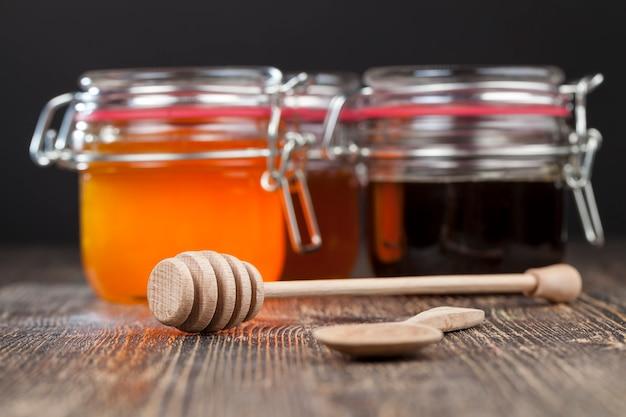Une cuillère à miel avec du miel d'abeille de haute qualité, une vieille table sur laquelle se trouve un miel d'abeille sain et sucré et une cuillère spéciale en bois