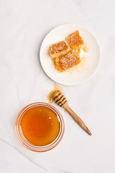 Cuillère à miel vue de dessus avec des morceaux de nid d'abeille