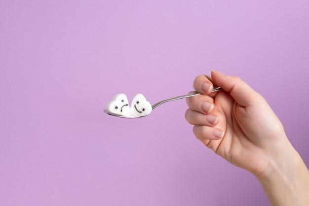 Cuillère avec un morceau de sucre dans une main féminine sur un fond lilas