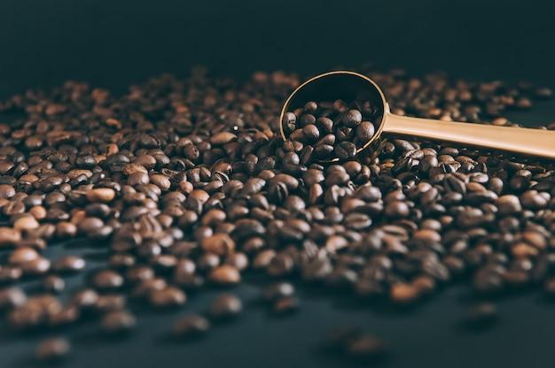 Cuillère d'or pour le monticule sur le fond avec des grains de café