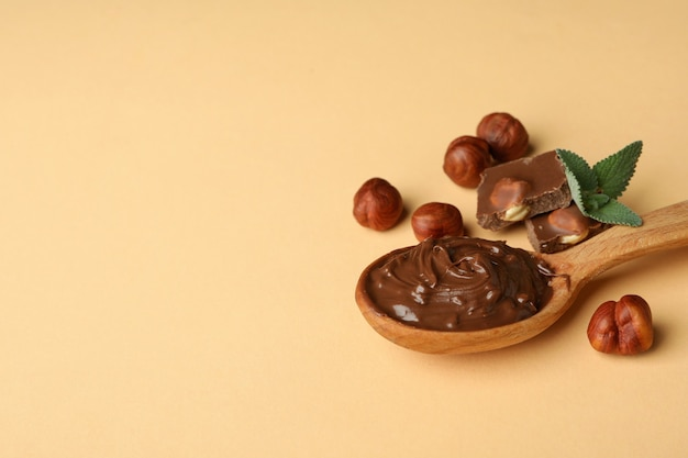 Cuillère à pâte de chocolat, noix, chocolat et menthe sur fond beige