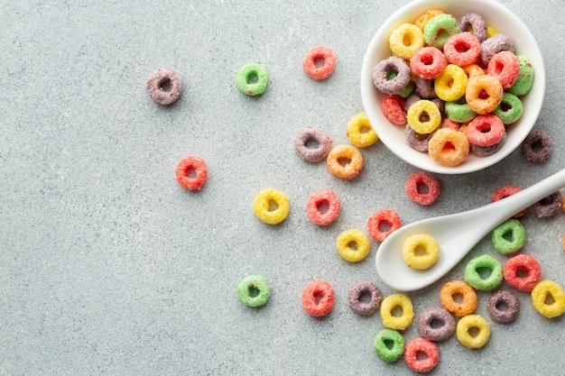Cuillère en plastique et céréales colorée vue de dessus