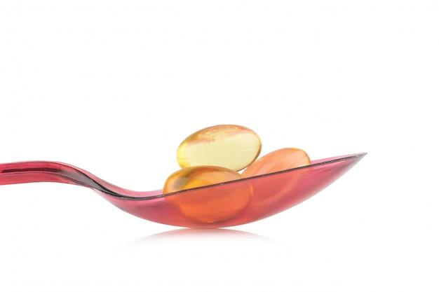 Cuillère en plastique rouge. isoler les capsules d'huile de poisson sur fond blanc