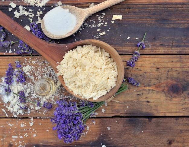 Cuillère pleine de flocons de savon avec de l'huile essentielle et un bouquet de fleurs de lavande