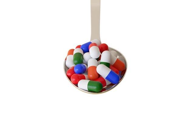 Cuillère pleine de pilules de couleurs différentes isolées.