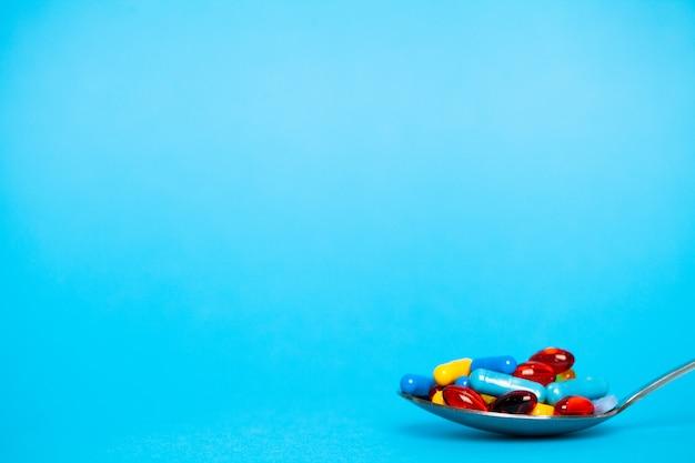 Cuillère Pleine De Pilules Pour Perdre Du Poids Sur Bleu Photo Premium