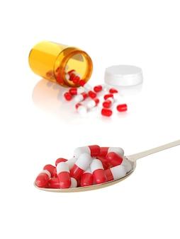 Cuillère pleine de pilules rouges et blanches et une bouteille de pilules renversée isolé sur fond blanc. mise au point sélective. concept d'abus de drogues.