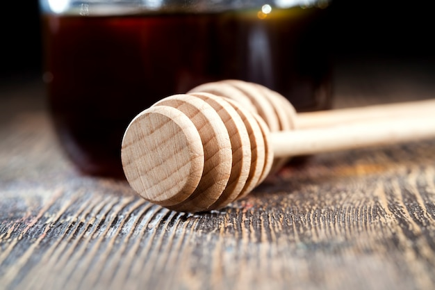Une cuillère pour le miel avec du miel d'abeille de haute qualité, une vieille table sur laquelle se trouve un miel d'abeille sain et sucré et une cuillère en bois maison qui vous permet de transférer et de verser le miel