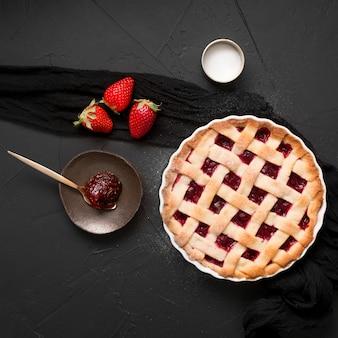 Cuillère remplie de confiture de fraises et vue de dessus de tarte