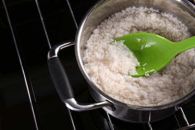 Cuillère à riz dans une poêle en métal sur plaque chauffante