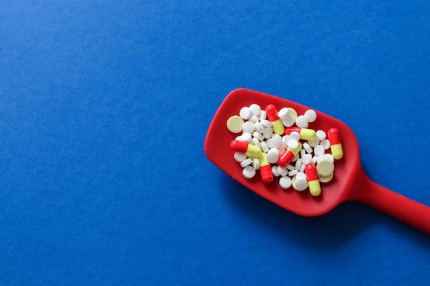 Cuillère rouge avec des pilules, des comprimés et des capsules de médicaments pharmaceutiques avec espace de copie