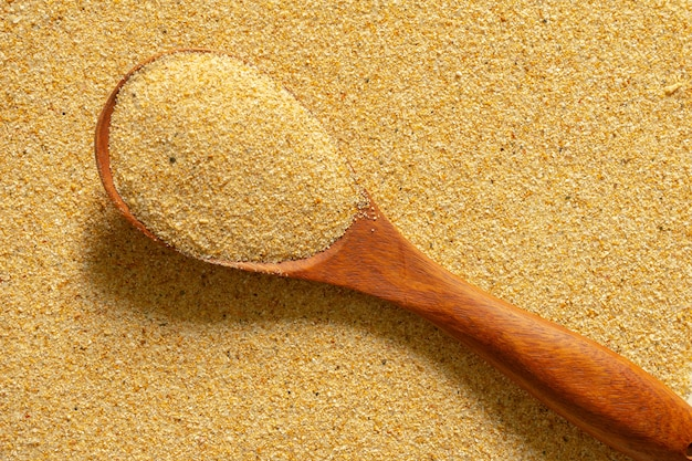 Cuillère à sable isolé studio tourné sur fond de sable.