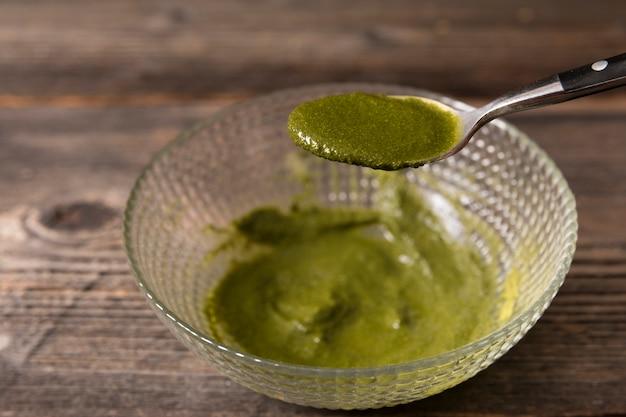 Cuillère à sauce verte au dessus du bol