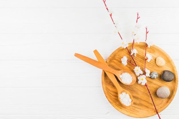 Cuillère à sel; fleurs et pierre spa sur planche de bois sur une surface blanche