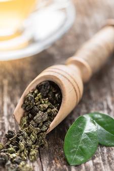 Cuillère de thé vert séché sur une table en bois
