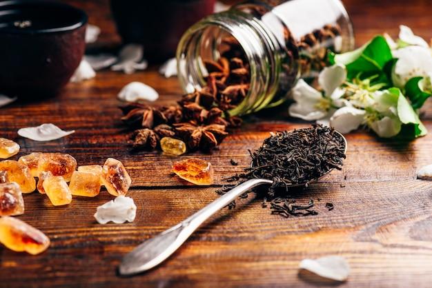 Cuillerée de thé, de fleurs de pommier, de sucre et d'étoile d'anis éparse sur une table en bois.
