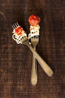 Cuillères en acier inoxydable croisées avec boulettes de viande et trenette sur table en bois