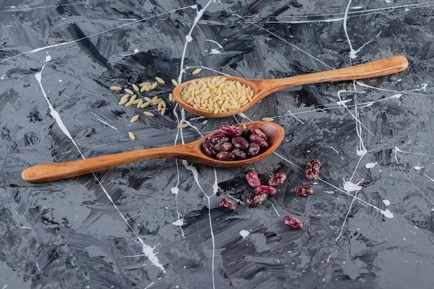 Cuillères en argent pleines de riz long et de haricots sur fond de marbre.