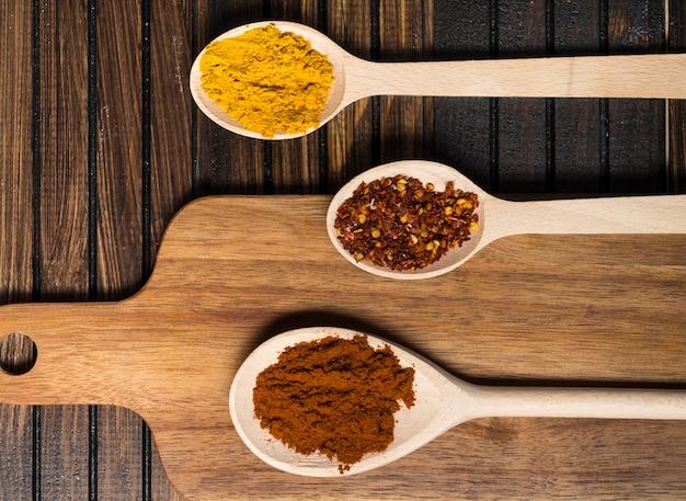 Cuillères aux épices chaudes près de la planche à découper