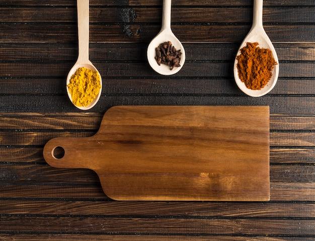 Cuillères aux épices près de la planche à découper