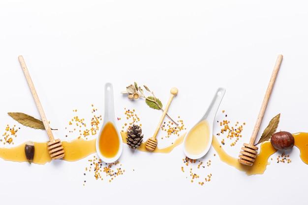 Cuillères blanches et bâtonnets de miel, avec du miel renversé