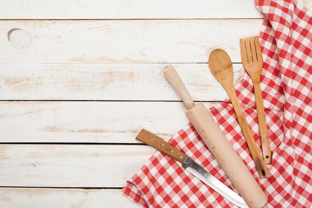 Cuillères en bois et autres ustensiles de cuisine avec des serviettes rouges sur la table de la cuisine.